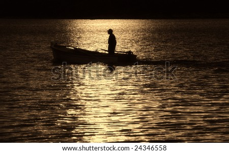 Silhouetted fisherman standing on a boat - stock photo