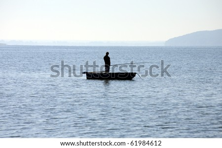 silhouetted fisherman standing on a boat, horizon - stock photo