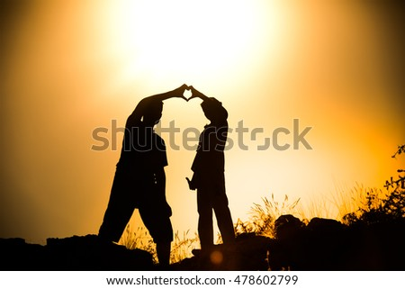 Silhouetted friend forming a heart symbol at golden hour sunset