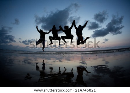 silhouetted friends jumping in sunset at beach  - stock photo
