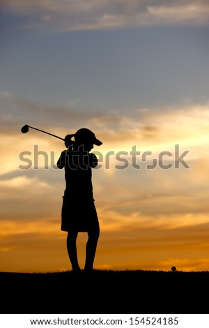 Silhouetted girl swings driver.