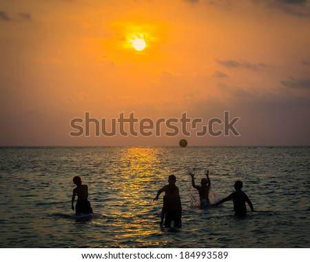 silhouetted group of boy are playing a ball in the sea during sunset