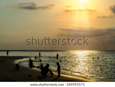 silhouetted group of people on the beach and in the sea under sunbeam in the evening with warm tone