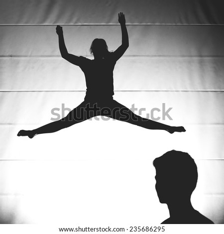 silhouetted gymnast jumping on trampoline  - stock photo