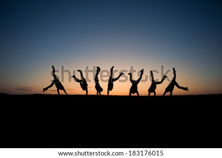 silhouetted gymnasts in sunset  - stock photo