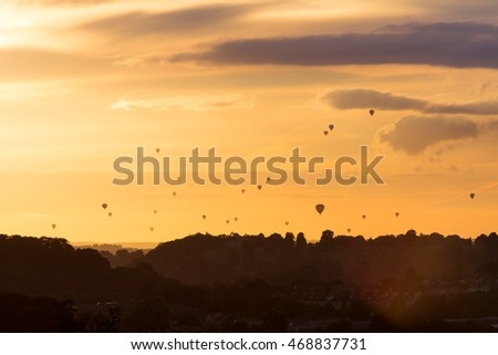 Silhouetted hot air balloons at sunset over the Avon Valley in Bristol during the mass ascent, part of the Bristol Balloon Fiesta on 13th August 2016.