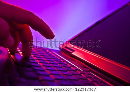 Silhouetted image someone typing on laptop computer Symbol shadow economy illegal operations cracking computer passwords fraud hacking advertising sales illegal non payment taxes concealment income - stock photo