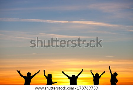 silhouetted kids in sunset  - stock photo