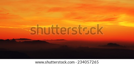 Silhouetted landscape panorama with warm sky at daybreak