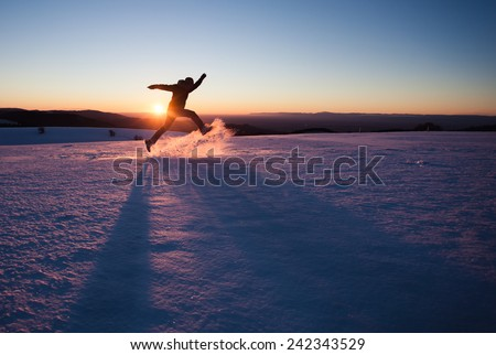 silhouetted man running through snow in winter landscape  - stock photo