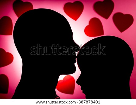 Silhouetted mannequin couple kiss against dark hearts background - stock photo
