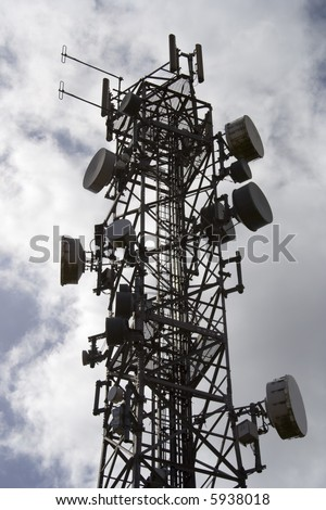 Silhouetted mobile cell phone transmitter aerial. This mast is covered in dishes and antenna. - stock photo