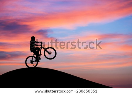 silhouetted mountainbiker doing wheelie in sunset sky on hill  - stock photo