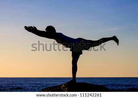 Silhouetted of asian man acts yoga on the beach in the morning