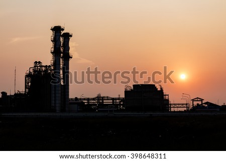 silhouetted of distillation towers at sunset