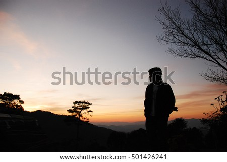 silhouetted of people standing in sunset