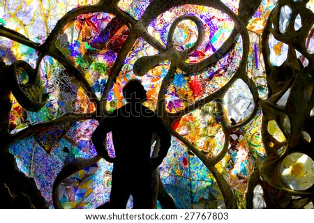 Silhouetted person stands before a wall of stained glass mural