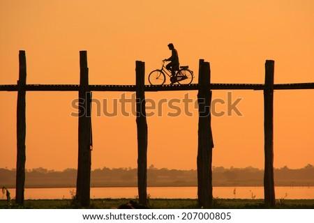 Silhouetted person with a bike on U Bein Bridge at sunset, Amarapura, Mandalay region, Myanmar - stock photo