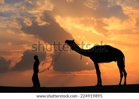 Silhouetted person with a camel at sunset, Thar desert near Jaisalmer, Rajasthan, India - stock photo