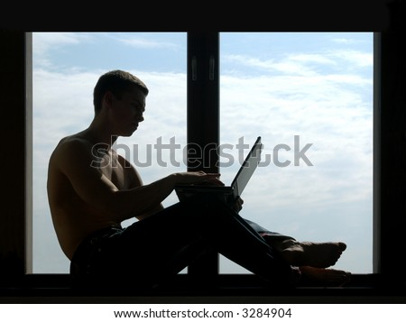 Silhouetted shirtless man working on a laptop sitting on the window-sill