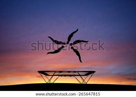 silhouetted trampoline gymnast  - stock photo