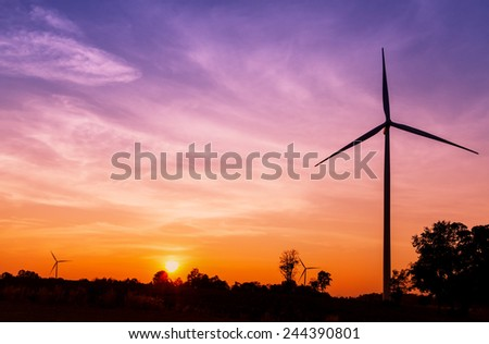 Silhouetted wind turbines power generator on sunset at farmer field - stock photo