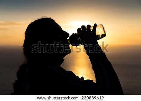 Silhouetted woman drinking water from a bottle at sunrsise