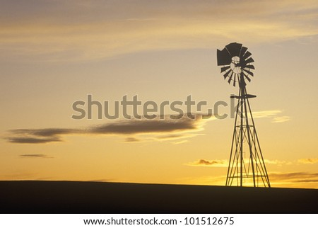 Silhouetted wooden windmill at sunset, South Dakota - stock photo