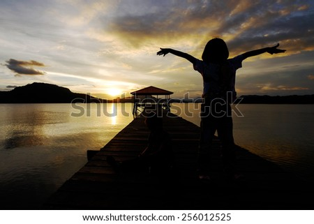 Silhouetted Young Girl Spreads her arm in enjoyment during sunrise at seaside wooden bridge at  - stock photo