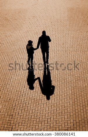 Silhouettes and shadows of  man and child holding hands on a pavement made of bricks - stock photo