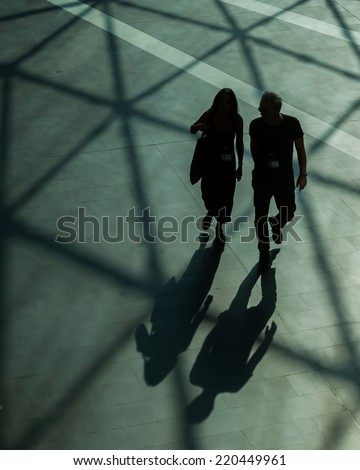 Silhouettes and shadows of people walking in a modern building