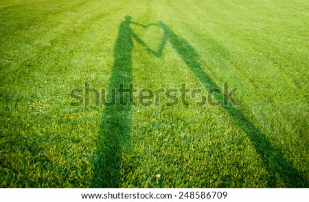 silhouettes forming a heart over grass - symbol of love - stock photo