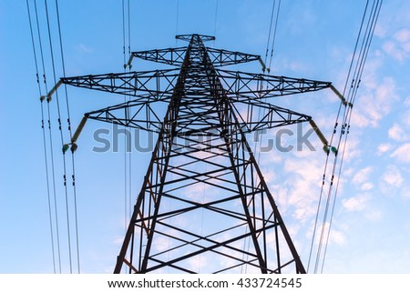 Silhouettes high voltage electric pylon in sunset background. - stock photo
