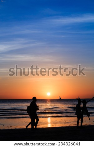 Silhouettes in front of a beautiful tropical sunset - stock photo