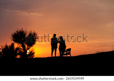 Silhouettes of a couple of girl and boy, backlit, in a park with the sun at sunset behind a Silhouette Couple at Sunset . Next to a bank in the parallel drive to the coast in Llanes Astourias