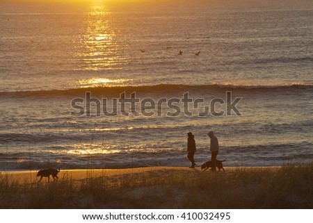 Silhouettes of a couple with two dogs walking along a scenic beach by the sea during a colorful sunrise early in the morning