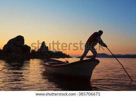 Silhouettes of a fisherman and rock formations in Lake Bafa near Bodrum, Mugla. The lake and the fishing boats in a very tranquil scene. Intentionally shot in backlit to create silhouettes. - stock photo