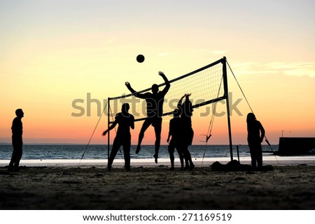 Silhouettes of a group of young people playing beach volleyball on the beach during sunset in Brittany, France - stock photo