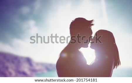 Silhouettes of a loving couple backlit by a bright sun in an intimate embrace staring into each others eyes as they prepare to kiss, mountain backdrop with copyspace - stock photo