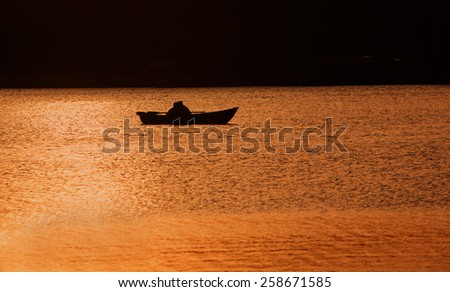 Silhouettes of a man and woman in the boat on the lake. Sunset. Light and shadow. Romance background.  - stock photo