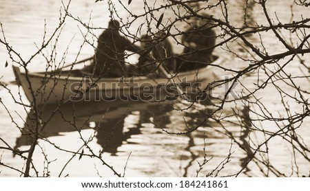 Silhouettes of  a man, woman and two kids in the boat on the lake. Twilight. Haze. Family background. Harmony with nature idea.  Aged photo. Sepia. Soft focus. - stock photo