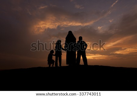silhouettes of a muslim women with her kid during sunset