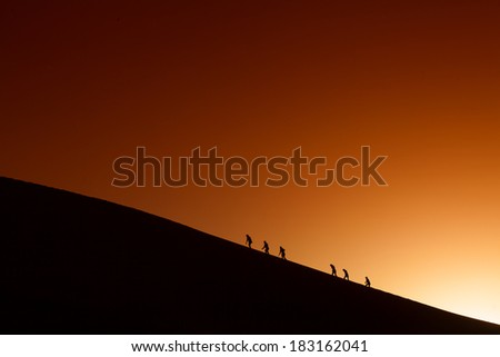 Silhouettes of a team on the mountain peak. Sport and active life - stock photo