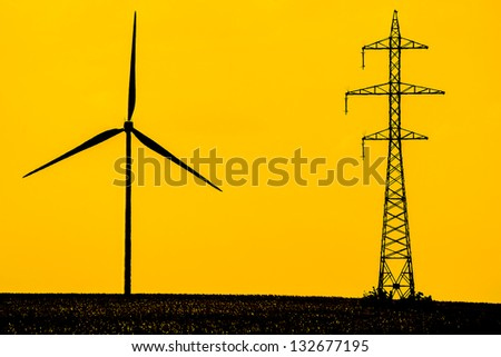 Silhouettes Of A Wind Turbine And Electrical Power Station Transmitter - stock photo