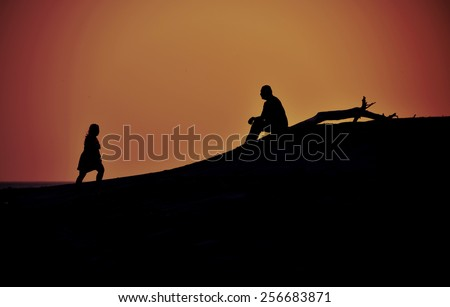 Silhouettes of a woman walking towards a man that is sitting at a beach during  sunset - stock photo