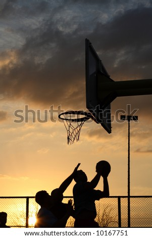 silhouettes of basketball players at the sunset - stock photo