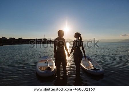 Silhouettes of beautiful couple with sup serf and paddle at the ocean