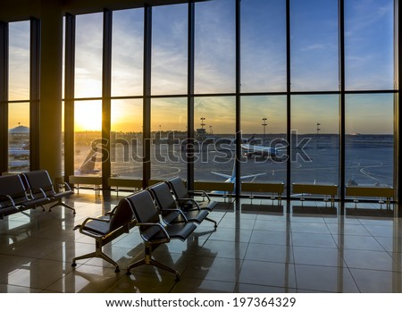 Silhouettes of bench in interior in airport lounge on background of the airfield with passenger planes - stock photo