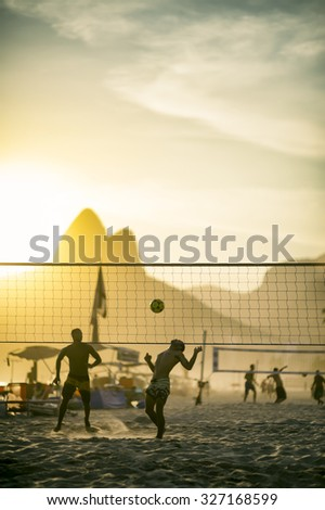 Silhouettes of Brazilians playing a beach ball game in the sand between volleyball nets against a backdrop of Dois Irmaos Mountain on Ipanema Beach, Rio de Janeiro Brazil  - stock photo
