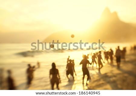 Silhouettes of Brazilians playing keepy uppy beach football soccer in golden sun Ipanema Beach Rio de Janeiro - stock photo